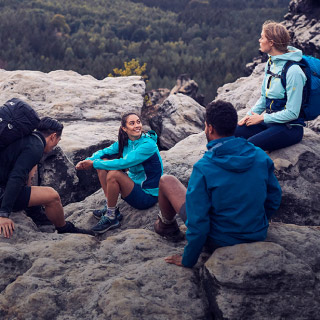 Wandergruppe sitzt auf Felsen