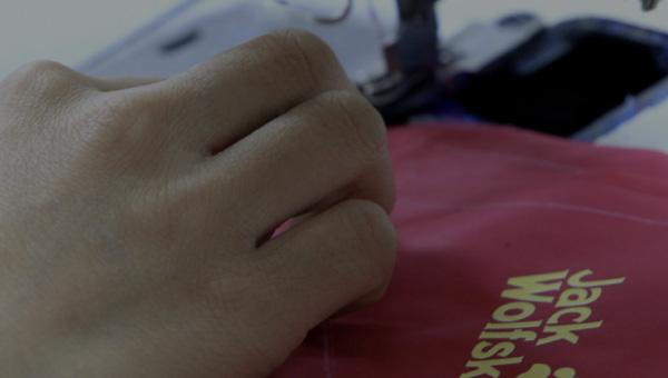 Nahaufnahme einer Hand mit einer Nähmaschine